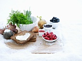 A still life of berries, wholemeal bread and herbs