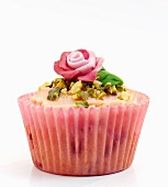 A celebration cupcake decorated with pistachios and a marzipan rose