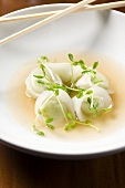 Edamame Dumplings in a Bowl of Broth with Chopsticks