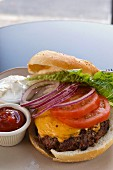 Cheeseburger with onions, tomatoes and lettuce, served with ketchup and mayonnaise