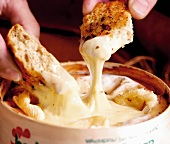 Hands dipping pieces of bread in melted Vacherin cheese
