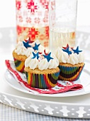 Cupcakes decorated with whipped cream and blue stars