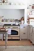 Vintage Küchenherd unter gemauertem Abzug in weisser Landhausküche