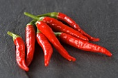 Mehrere frische rote Chilischoten auf Schieferplatte