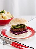 Turkey burger with red cabbage and courgette, served with potato salad