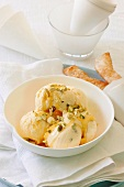 Passion fruit ice cream with syrup and chopped pistachios
