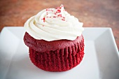 A Red Velvet Cupcake with White Frosting and Red Sugar Crystals