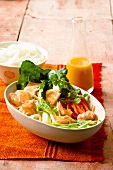 A salad of rice noodles with salmon and sweet and sour sauce