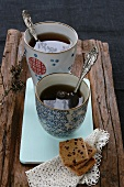 Chinese tea mugs, shortcakes and a doily on a piece of wood