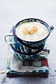 Creamy apple and celeriac soup with poppy seeds and scallops