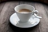 Eine Tasse Milchkaffee auf Holzuntergrund