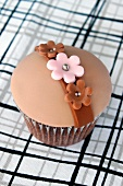 A chocolate cupcake with caramel filling, topped with fondant icing