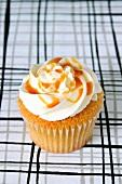A vanilla cupcake with caramel sauce