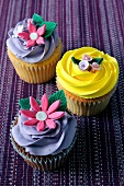 A chocolate cupcake and a lemon cupcake topped with decorative flowers