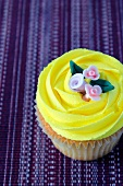 A lemon cupcake with sugar flowers