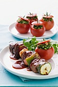 Beef skewers with vegetables and halloumi, and tomatoes stuffed with tabbouleh