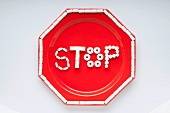 The Word Stop Spelled Out with White Candies on a Red Plate; From Above; White Background