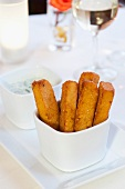 Polenta Fries Standing in a White Dish with a Dish of Dipping Sauce; White Wine
