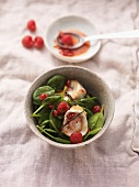 Spinach salad with turkey breast, raspberries and pomegranate seeds