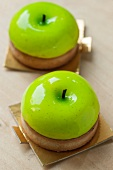 Two individual Apple pies covered with round vanilla panacotta, imitating half an apple.