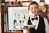 A waiter holding a tray with two glasses of sparkling wine in a restaurant