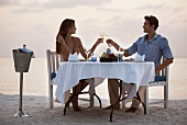 Paar stösst mit Sektgläsern an beim Dinner for Two am Sandstrand
