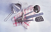 Assorted kitchen utensils on a tea towel
