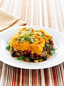 A Serving of Shepherd's Pie Topped with Sweet Potato on a White Plate