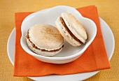 Two Dulce de Leche Macaroons in a White Bowl on an Orange Napkin