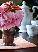 Cherry Blossoms in a Vase with Antique Tea Setting in Background
