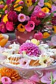 Farbenfroher Sommerblumenstrauss vor festlicher Etagere mit frischem Gebäck und prachtvoller Dahlie