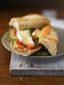 A baguette sandwich filled with brie and tomatoes