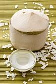 Geschälte Kokosnuss, Kokoswasser und Kokosraspeln auf Bambusmatte