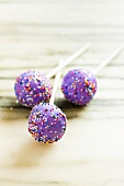 Three Purple Frosted Cake Pops with Rainbow Colored Sprinkles