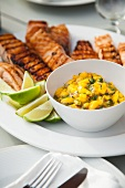 Grilled Salmon with Mango Salsa and Lime Wedges on a Platter on a Table