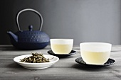 Two Cups of Green Tea, loose Tea and Japanese Teapot, selective focus