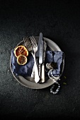 A tin plate with a blue cloth, antique cutlery, a necklace and dried citrus fruits