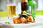 A chicken skewer with salad, served with a glass of beer