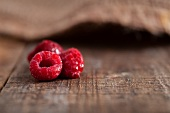 Three frozen raspberries on a rustic surface