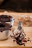 Chocolate melting middle puddings; an egg whisk with remnants of the raw mixture to one side