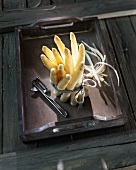 A bunch of white asparagus with a peeler on a wooden tray