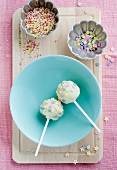 Cake pops covered in white chocolate with chocolate stars and sugar confetti