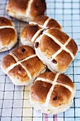 Several hot cross buns on a cooling rack