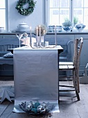 A table laid in silver - lit candles with glasses and plates on a table runner made from silver paper, with vintage wooden chairs pulled up to the table
