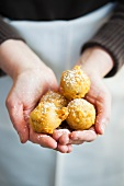 Hands Holding Beignets Sprinkled with Powdered Sugar
