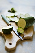 A courgette, partly sliced, on a chopping board