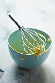 Egg whisk with remains of mayonnaise, laid across the top of the bowl