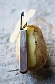 A potato, partly peeled, with a potato peeler