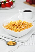 Cornflakes with milk in a heart-shaped bowl