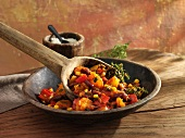 Bean stew with kidney beans, peppers and sweetcorn in a wooden bowl